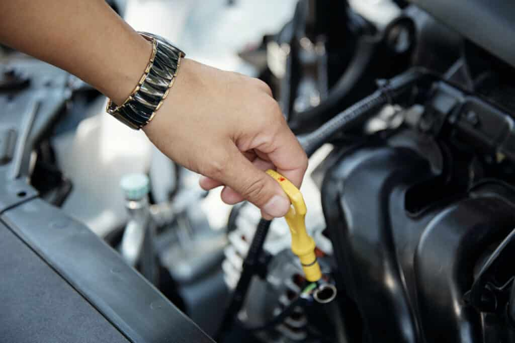 Car owner checking oil level in car engine
